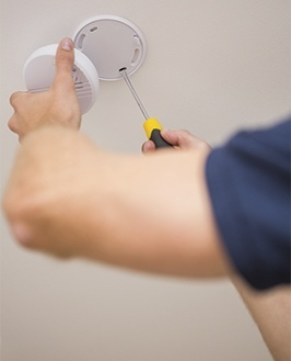 Persona instalando un detector de humos. Detección de incendios en Málaga